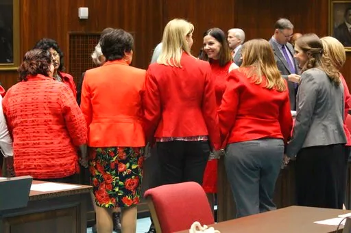 Female members of the Arizona House, from Republican and Democratic parties, hold hands to express support for Rep. Michelle Ugenti-Rita, middle facing camera, as the House prepares to vote to expel Don Shooter. (Source: AP Photo/Bob Christie)