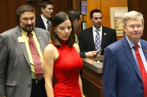 Arizona state Rep. Michelle Ugenti-Rita, center, leaves the House speaker's office along with Reps. Jay Lawrence, left, and Vince Leach, right, in Phoenix, Ariz., Thursday, Feb. 1, 2018. (AP Photo/Bob Christie)