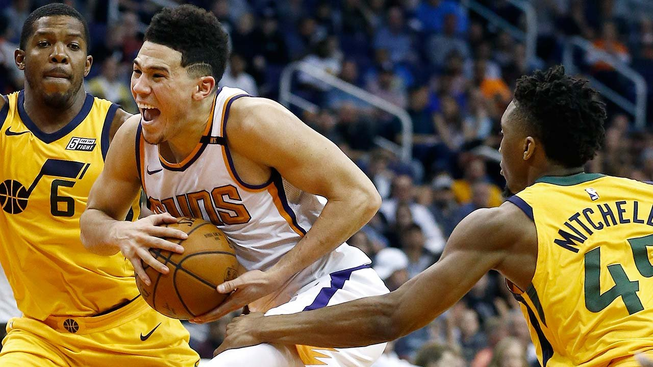 Phoenix Suns guard Devin Booker, middle, is fouled by Utah Jazz guard Donovan Mitchell, right, as Jazz guard Joe Johnson (6) helps defend during the second half of an NBA basketball game Friday, Feb. 2, 2018. (Source: AP Photo/Ross D. Franklin)