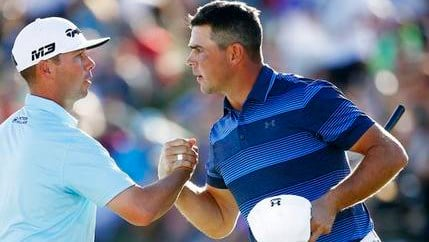 After winning a one-hole playoff, Gary Woodland, right, shakes hands with Chez Reavie, left, on the 18th green during the final round of the Waste Management Phoenix Open golf tournament Feb. 4, 2018, in Scottsdale, Ariz. (AP Photo/Ross D. Franklin)