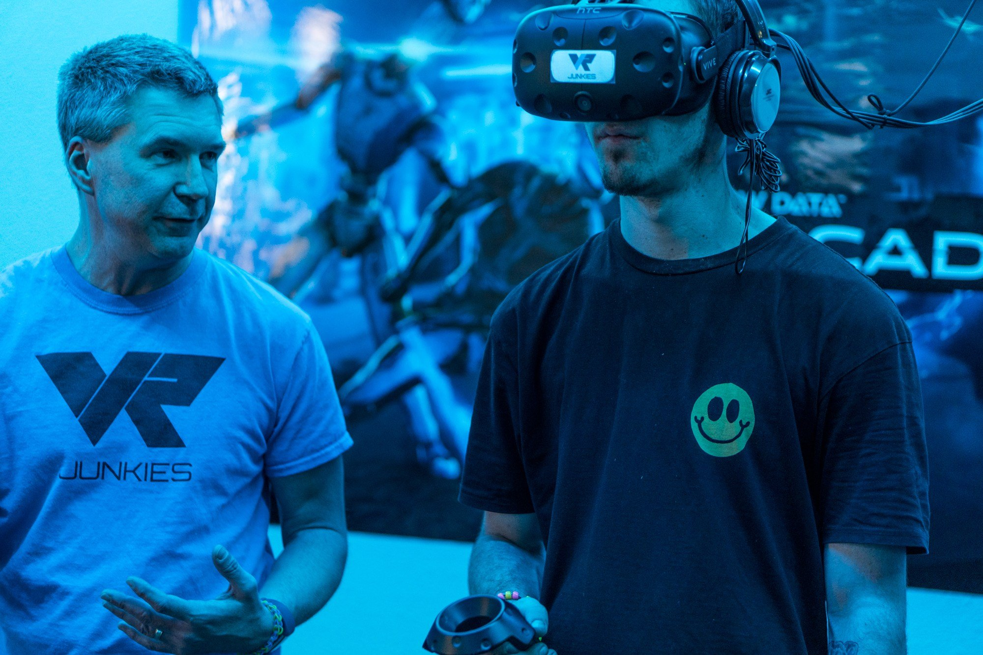 """Chris Krakowsk (left), co-owner of VR Junkies in Tempe, explains to Tyler Powell how to play """"Arizona Sunshine,"""" a post-apocalyptic VR zombie shooter game. (Source: Daria Kadovik/Cronkite News)"""