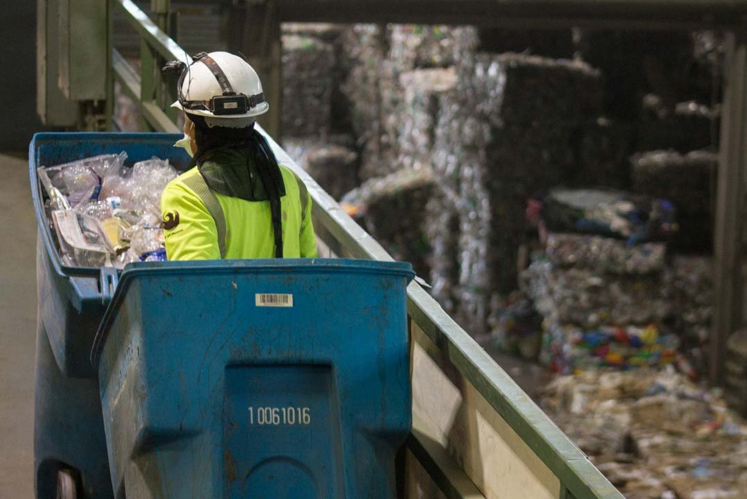 A worker at the 27th Avenue Transfer Station in Phoenix moves bins full of plastic material. (Source: by Miles Metke/Cronkite News)