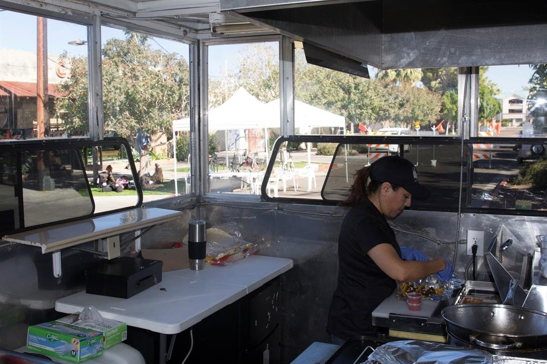 Co-owner Leticia Gamiz prepares an order of tacos inside her food truck. (Source: Andrea Estrada/Cronkite News)