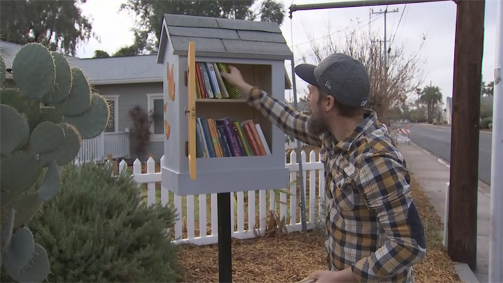 Nick Barnhiser puts new books in the rebuilt Little Free Library in front of his house. (Source: 3TV/CBS 5)