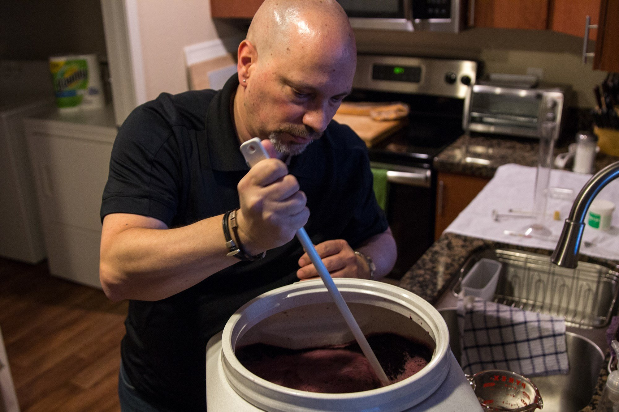 Louis Marconi, a member of AZ Winemakers, a association of home wine makers, works on a batch at his Chandler home. After the wine is fermented, Marconi filters powders and removes impurities. (Source: Jenna Miller/ Cronkite News)