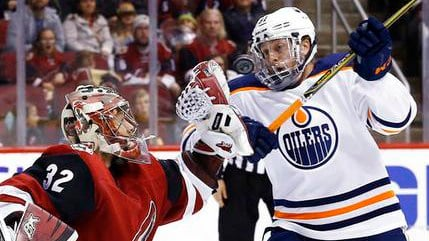 Arizona Coyotes goaltender Antti Raanta (32) reaches out to catch the puck as it gets by Edmonton Oilers left wing Drake Caggiula (91) during the first period of an NHL hockey game Saturday, Feb. 17, 2018, in Glendale, Ariz. (AP Photo/Ross D. Franklin)
