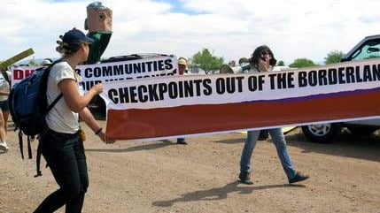FILE - In this May 27, 2015, file photo, two protesters carry a large banner as they walk toward a U.S. Border Patrol checkpoint on a two-lane road in Amado, Ariz., about 20 miles north of the Mexican border. (Source: AP Photo/Astrid Galvan, File)