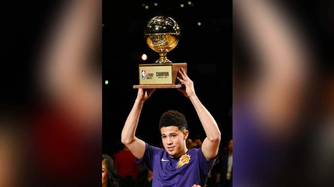 Phoenix Suns' Devin Booker holds up his trophy after winning the NBA All-Star basketball Three Point contest, Saturday, Feb. 17, 2018, in Los Angeles. (Source: AP Photo/Chris Pizzello)