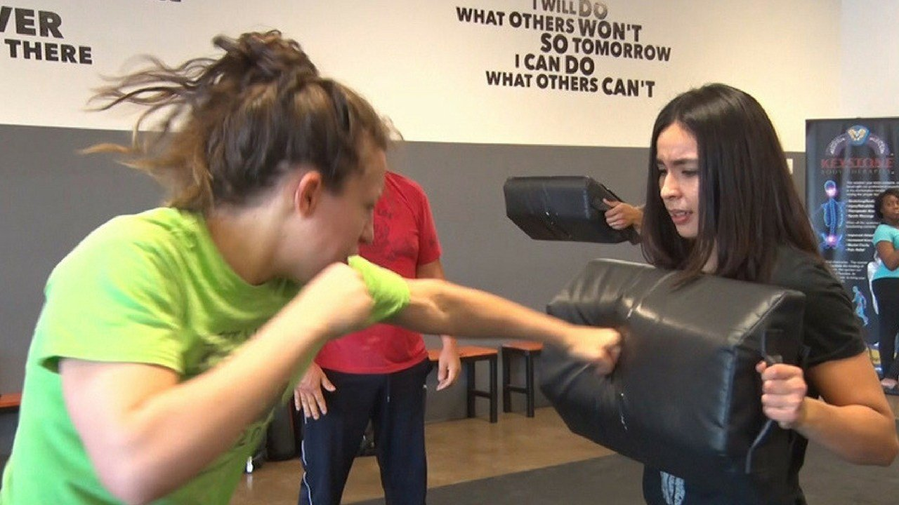 Ivvette Rios Hofrichter (right), a Krav Maga instructor at East Valley Krav Maga, practices drills with a student at the Tempe facility. (Photo by Nicole Gutierrez/Cronkite News)
