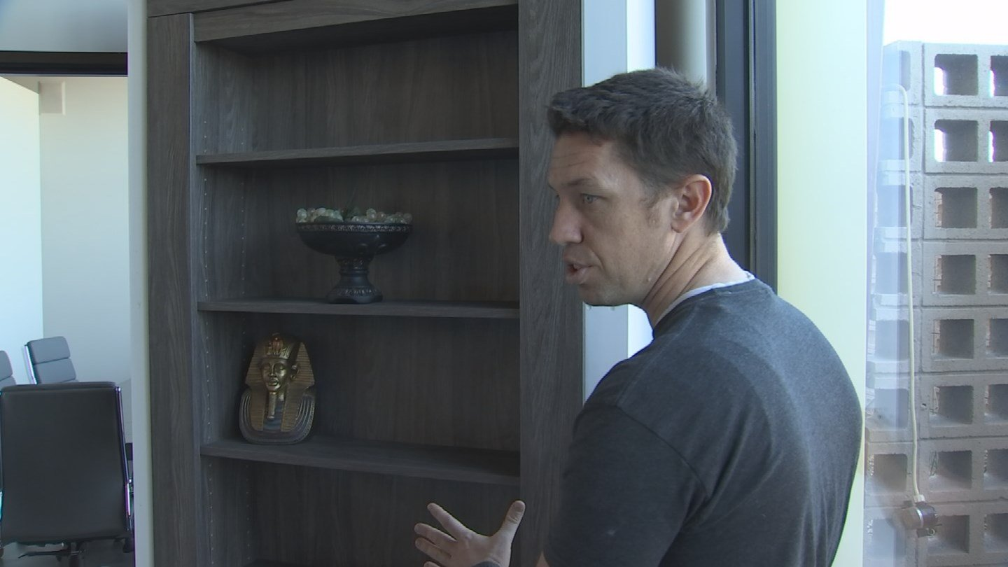 Steve Humble of Creative Home Engineering shows Jason Barry one of many secret doors that look like anything but doors. (Source: 3TV/CSB 5)