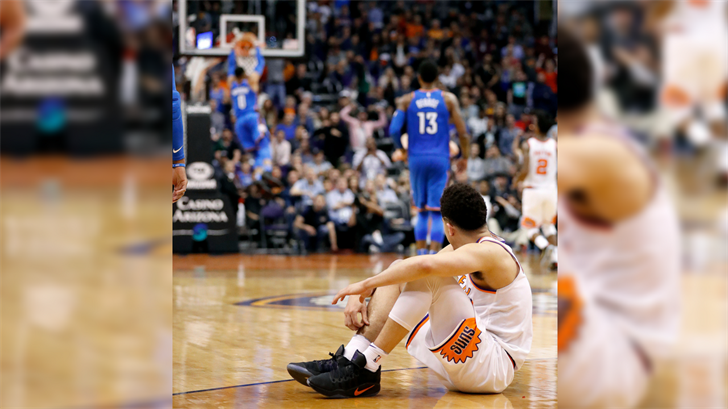 Phoenix Suns guard Devin Booker watches Oklahoma City Thunder guard Russell Westbrook (0) dunk after a turnover during the final seconds during the second half. (Source: AP Photo/Matt York)
