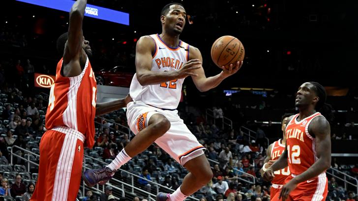 Phoenix Suns forward TJ Warren shoots while flanked by the defense of Atlanta Hawks center Dewayne Dedmon, left, and forward Taurean Prince (12). (Source: AP Photo/John Amis)