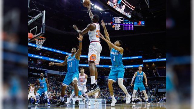 Phoenix Suns guard Davon Reed, center, shoots over the double team by Charlotte Hornets center Dwight Howard (12) and guard Jeremy Lamb in the first half of an NBA basketball game in Charlotte, N.C., Saturday, March 10, 2018. (AP Photo/Nell Redmond)