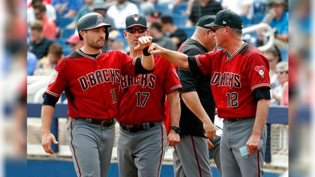 Arizona Diamondbacks' A.J. Pollock (11) is greeted by bench coach Jerry Narron (12) after scoring on a sacrifice fly by Jake Lamb during the first inning of a spring training baseball game against the Milwaukee Brewers, March 8, 2018. (AP Photo/Matt York)