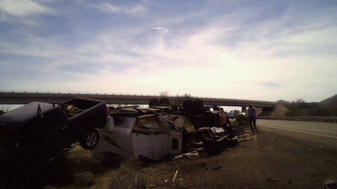 DPS investigators looking over wreckage of pickup truck with camper that flipped on I-10 Monday. (Source:Arizona Dept. of Public Safety)