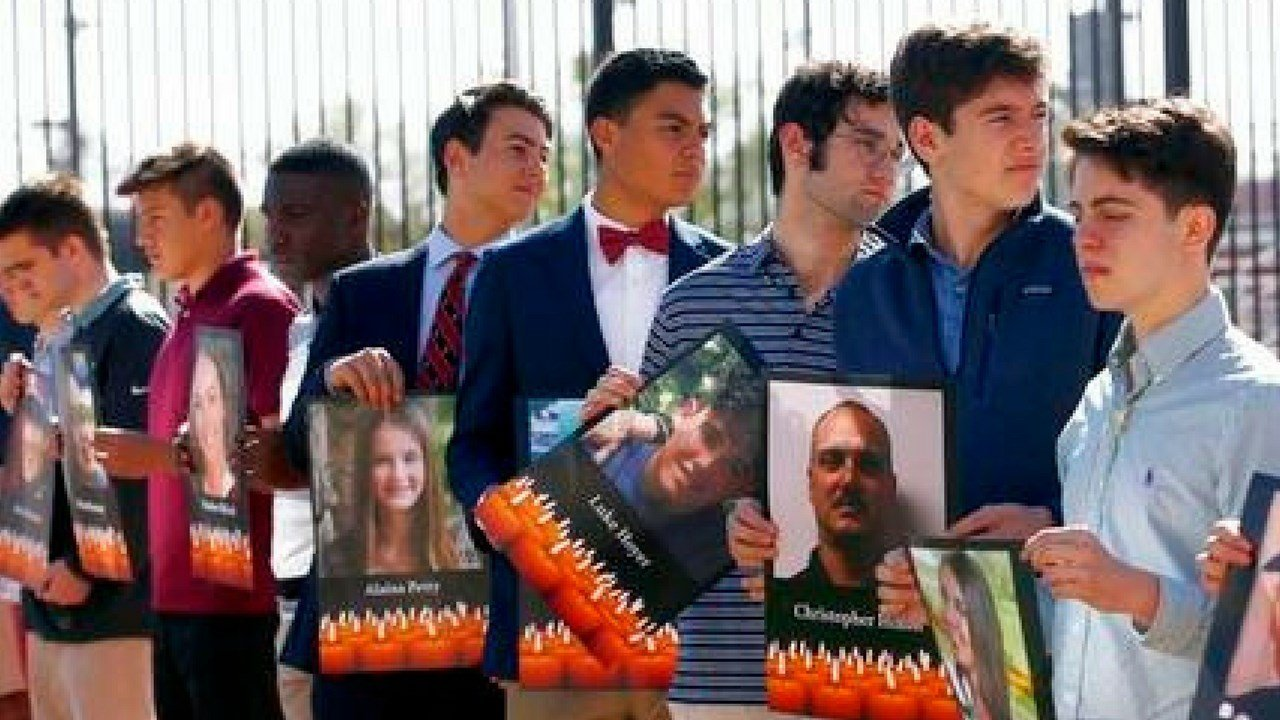 Students hold up pictures of the 17 victims killed in a recent school shooting in Florida and demand action regarding gun violence during a gathering at Brophy College Preparatory high school Wednesday, March 14, 2018, in Phoenix. (AP Photo/Ross D. Frankl
