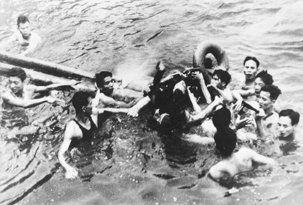 Sen. John McCain is pulled out of a Hanoi lake by North Vietnamese soldiers and civilians on October 26, 1967. McCain's A-4E Skyhawk was shot down by a surface-to-air missile. He broke both arms and his right knee upon ejection. (Source: Getty Images)