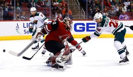 Minnesota Wild right wing Nino Niederreiter (22) scores a goal against Arizona Coyotes goaltender Antti Raanta (32) as Wild left wing Jason Zucker (16) looks on during the first period of an NHL hockey game March 17, 2018. (AP Photo/Ross D. Franklin)