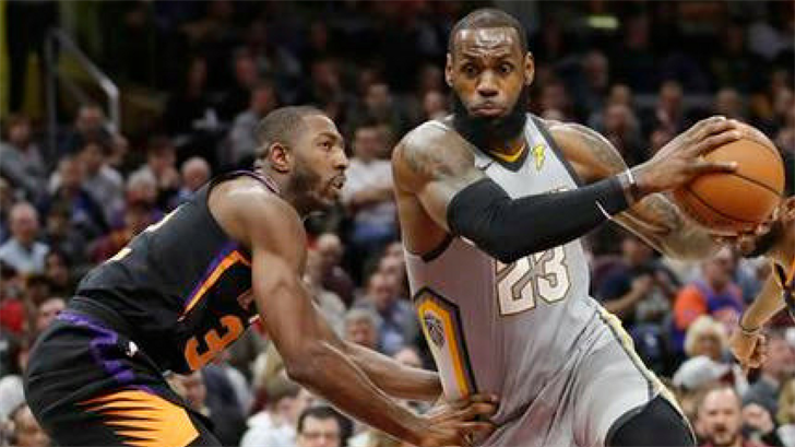 Cleveland Cavaliers' LeBron James, right, drives past Phoenix Suns' Davon Reed during the second half of an NBA basketball game Friday, March 23, 2018, in Cleveland. The Cavaliers won 120-95. (Source: AP Photo/Tony Dejak)
