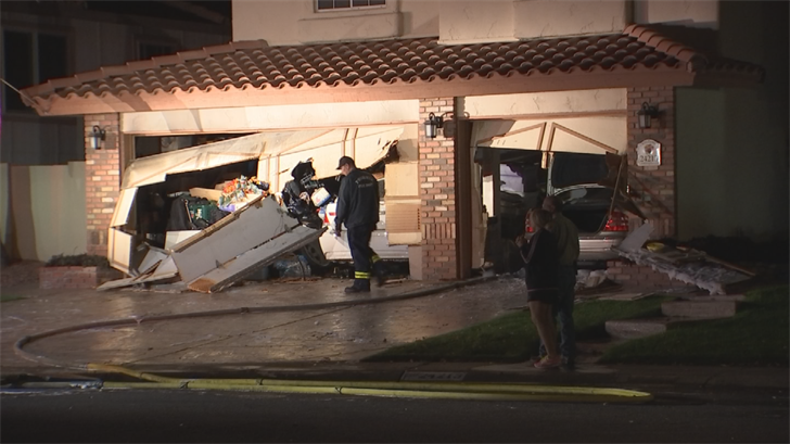 Firefighters had to cut open the garage doors to access the car fire. (Source: 3TV/CBS 5)