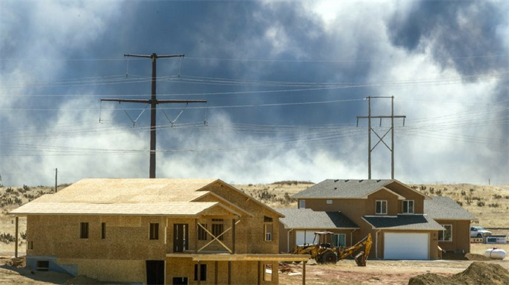 Smoke rises from a wildfire that started on Fort Carson behind homes in Colorado. The Army said Monday, March 26, that the wildfire was sparked by live fire training at Fort Carson. (Dougal Brownlie/The Gazette via AP)