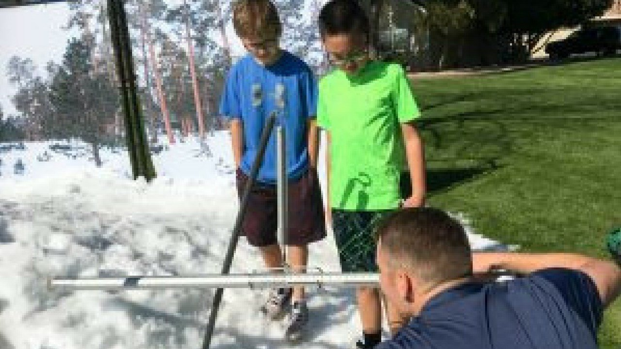 Two boys look on as an SRP employee shows how to measure snowpack. (Photo by Casey Kuhn/KJZZ)