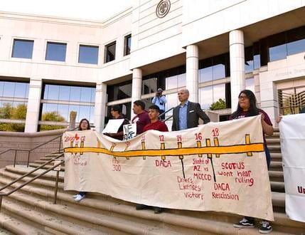 Immigrant students with deferred deportation status hold a banner in support asking the Supreme Court to rule in favor of continuing their access to in-state tuition costs. (Source: AP Photo/Anita Snow)
