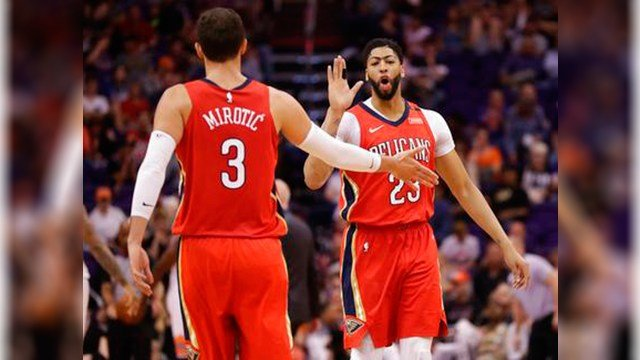 New Orleans Pelicans forward Anthony Davis (23) slaps hands with Nikola Mirotic (3) during the second half of the team's NBA basketball game against the Phoenix Suns on Friday, April 6, 2018, in Phoenix. (Source: AP Photo/Matt York)
