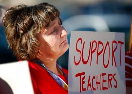 "Nanette Swanson pauses as she listens to another teacher at Tuscano Elementary School as teachers, parents and students stage a ""walk-in"" for higher pay and school funding Wednesday, April 11, 2018, in Phoenix. (Source: AP Photo/Ross D. Franklin)"