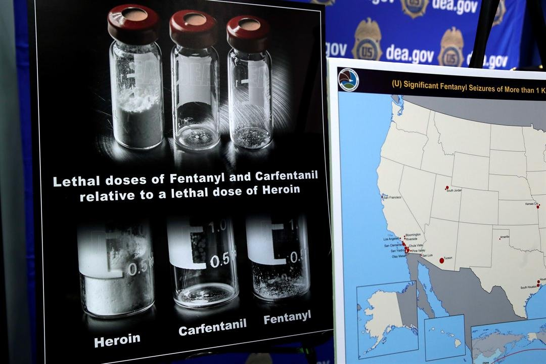 Posters comparing lethal amounts of heroin, fentanyl, and carfentanil, are on display during a news conference about the dangers of fentanyl, at DEA Headquarters in Arlington Va., Tuesday, June 6, 2017. (Source: AP Photo/Jacquelyn Martin)