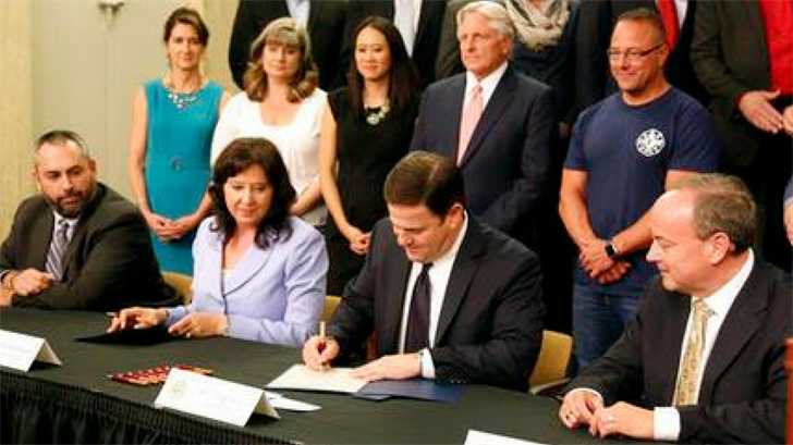 FILE- In this May 26, 2016, file photo, Arizona Gov. Doug Ducey, second from right, signs a proclamation certifying the results of Proposition 123 on school funding at the state Capitol in Phoenix. (Source: AP Photo/Ryan Van Velzer, File)