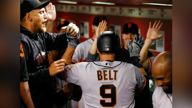 San Francisco Giants' Brandon Belt (9) celebrates his two-run home run against the Arizona Diamondbacks with Hunter Pence, left, and other teammates during the 10th inning Wednesday, April 18, 2018, in Phoenix. (Source: AP Photo/Ross D. Franklin)