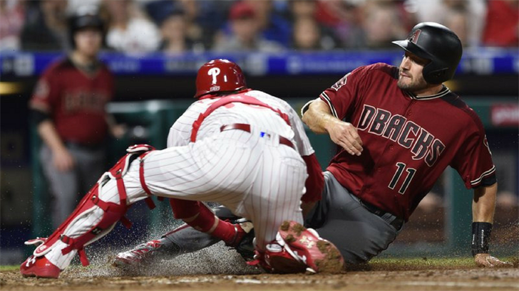 Arizona Diamondbacks' A.J. Pollock, right, is tagged out at home plate by Philadelphia Phillies' Andrew Knapp after Jarrod Dyson hit a fielders choice during the fourth inning of a baseball game. (Source: AP Photo/Derik Hamilton)