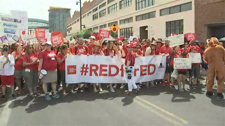 On the first day of the historic statewide walkout, around 50,000 educators and their supporters marched Thursday through downtown Phoenix in nearly 100-degree heat and swarmed the Capitol grounds. (Source: 3TV/CBS 5)