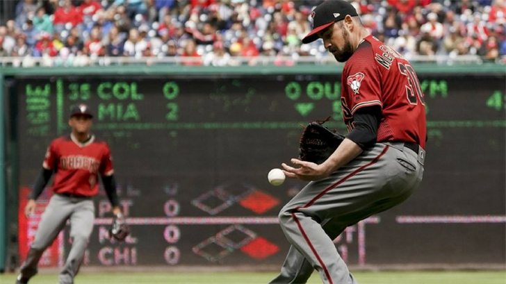 Arizona Diamondbacks relief pitcher T.J. McFarland (30) bobbles a ball hit by Washington Nationals' Ryan Zimmerman during the second inning of a baseball game at Nationals Park Sunday, April 29, 2018, in Washington. (Source: AP Photo/Andrew Harnik)
