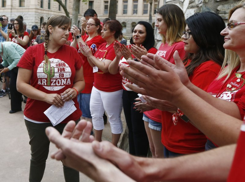Phoenix teacher Rebecca Garelli, left, an Arizona Educators United member, is applauded after her announcement from protest organizers that teachers intend to go back to work. (Source: AP Photo/Ross D. Franklin)