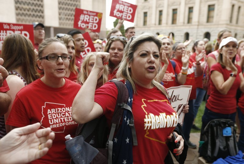 Arizona teacher Aurelia Ionescu, front right, chants with other teachers as protest organizers announce their intention to go back to work as the state-wide teachers strike enters a fourth day. (Source: AP Photo/Ross D. Franklin)