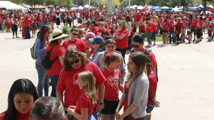 Striking Arizona teachers, many with their children in tow, line up to enter the old state Capitol building in Phoenix, Wednesday, May 2, 2018. Teachers are in the fifth day of a statewide strike. (Source: AP Photo/Bob Christie)