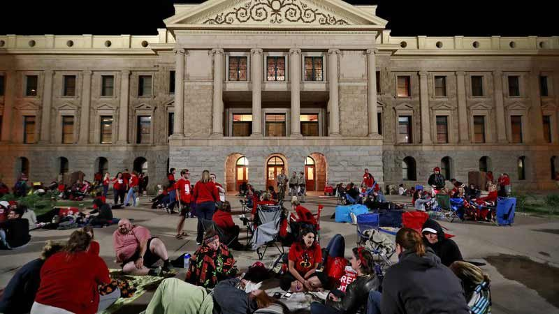 Teachers camp out as the Arizona legislature debates a budget negotiated by majority Republicans and GOP Gov. Doug Ducey Thursday, May 3, 2018, at the Capitol in Phoenix. (Source: Matt York, AP)