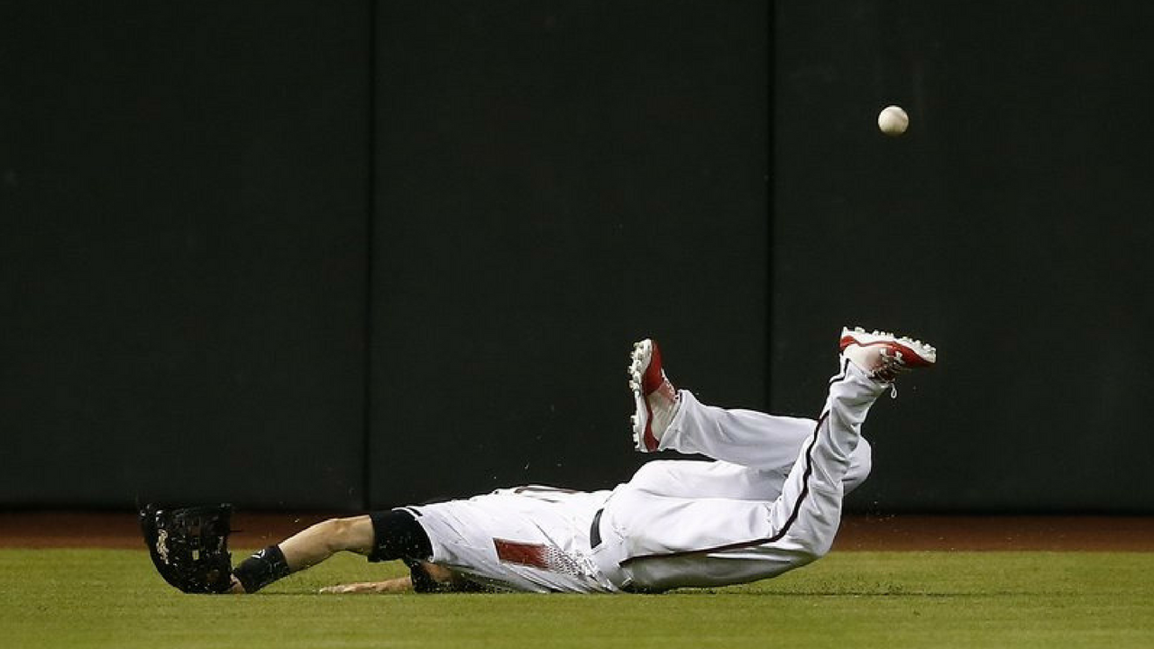Arizona Diamondbacks center fielder A.J. Pollock lands awkwardly as he dives for a line drive hit by Milwaukee Brewers' Tyler Saladino during the ninth inning of a baseball game Monday