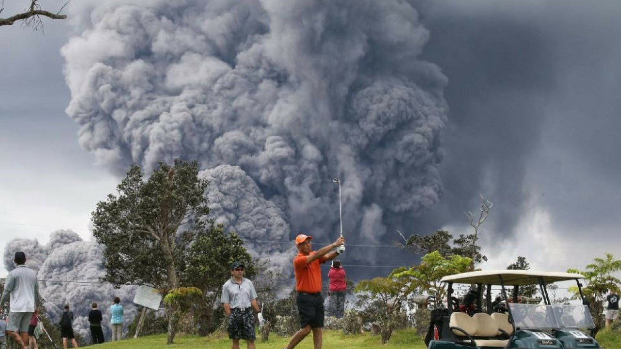 People play golf as an ash plume rises in the distance from the Kilauea volcano on Hawaii's Big Island (Source:CNN)