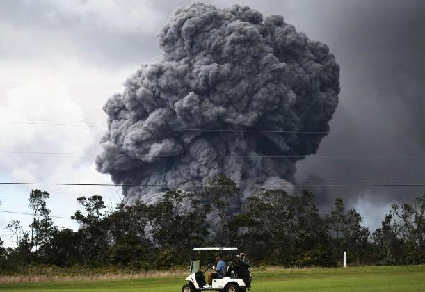 A man drives a golf cart at a golf course as an ash plume rises in the distance from the Kilauea volcano on Hawaii's Big Island (Source: CNN)