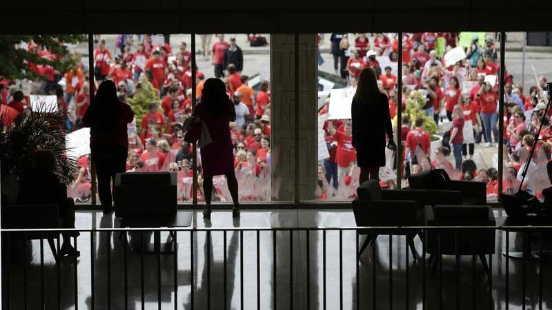 People watch from inside the Legislative Building as participants gather during a teachers rally at the General Assembly in Raleigh, N.C., Wednesday, May 16, 2018. (Source: Gerry Broome, AP)
