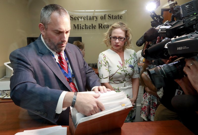U.S. Rep. Kyrsten Sinema, D-Ariz., delivers her signatures to Arizona Director of Elections Eric Spencer at the Arizona Secretary of State's office Tuesday, May 29, 2018 at the Capitol in Phoenix. (Source: AP Photo/Matt York)