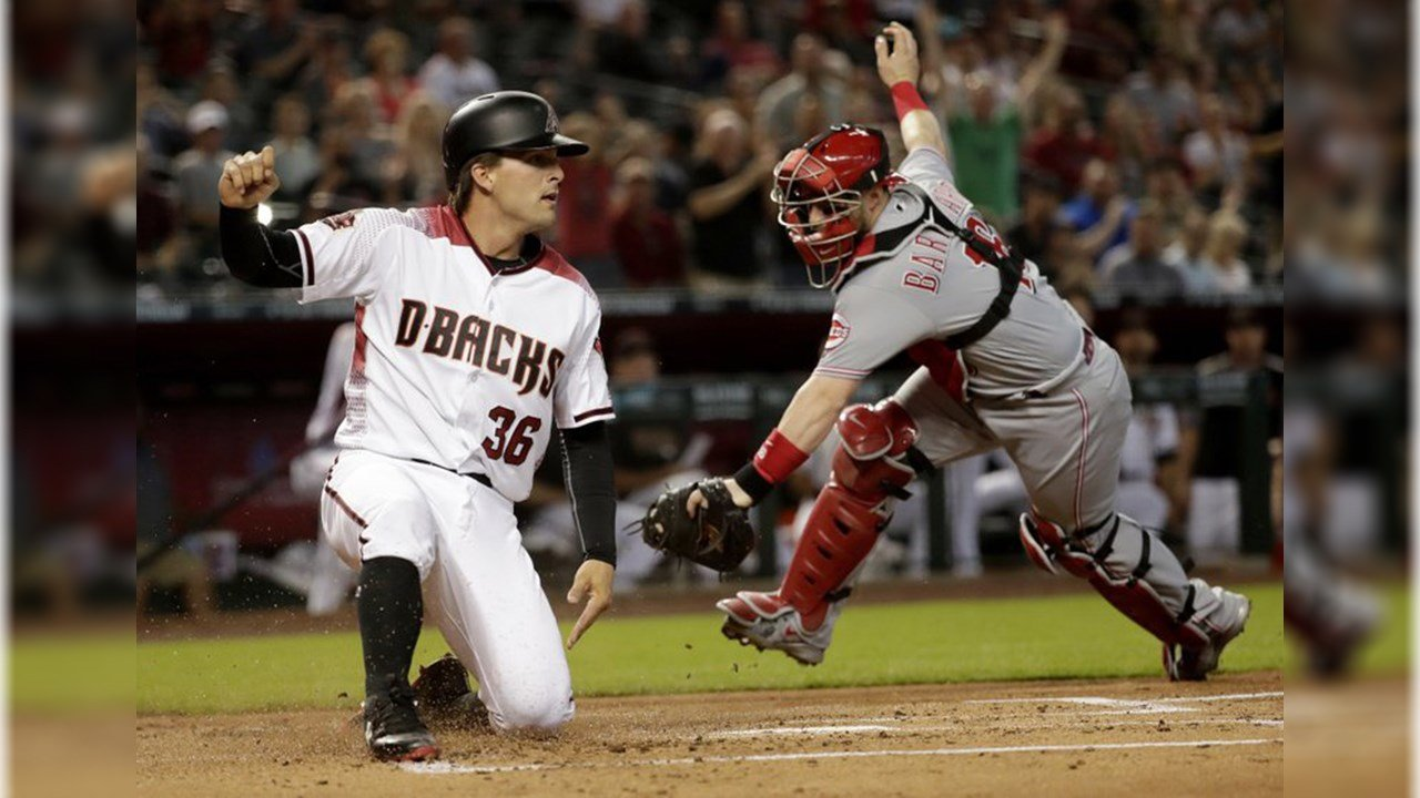 Arizona Diamondbacks' John Ryan Murphy (36) scores on a double by David Peralta as Cincinnati Reds catcher Tucker Barnhart misses the tag during the first inning of a baseball game Wednesday, May 30, 2018, in Phoenix. (Source: AP Photo/Matt York)