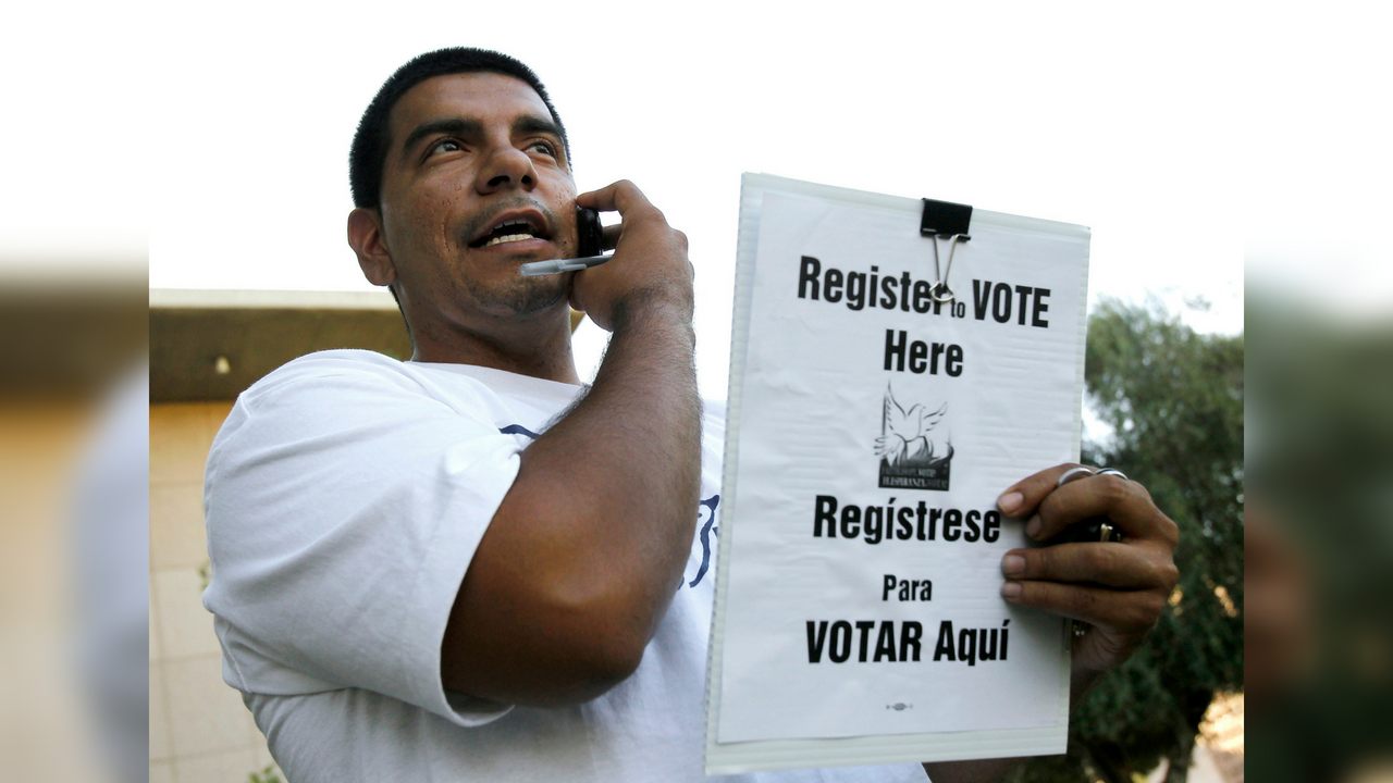 Volunteer Tomas Robles, for Promise Arizona, talks to a potential voter he wants to visit, as the group holds a voter registration rally at the Arizona Capitol Friday, Oct. 1, 2010, in Phoenix. (Source: AP Photo/Ross D. Franklin)
