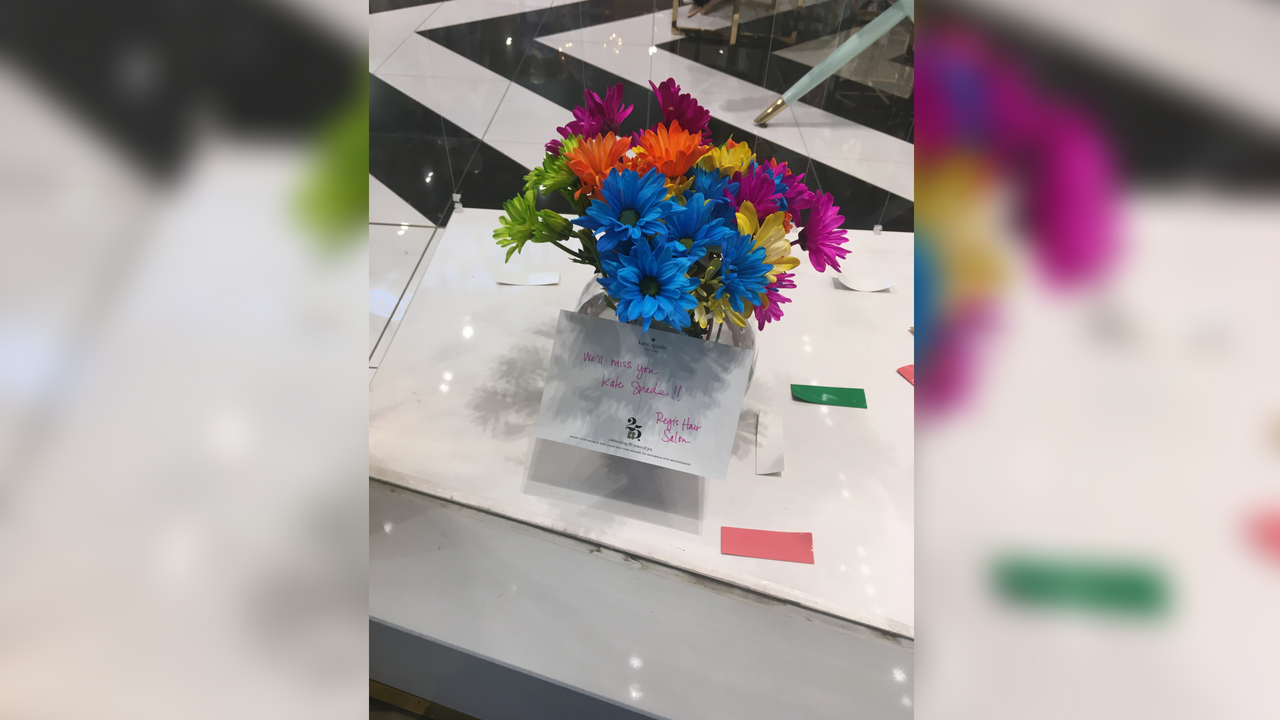 "At the Scottsdale Fashion Square location, a single vase of flowers sits in the front window, sent over from a neighboring salon with a note that reads ""We'll miss you, Kate Spade."" (Source: 3TV/CBS 5)"