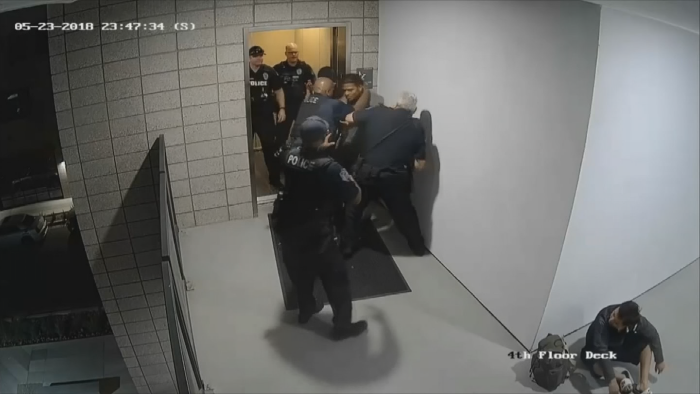Audio-free surveillance footage from the apartment complex where the incident took place shows Johnson standing against a wall, looking at his phone, while Reyes is sitting on the ground nearby. (Source: Mesa Police Department)