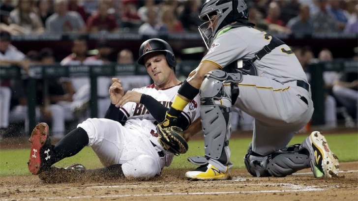 Arizona Diamondbacks' John Ryan Murphy is tagged out by Pittsburgh Pirates catcher Elias Diaz while trying to score on a base hit by Chris Owings during the second inning of a baseball game, Monday, June 11, 2018, in Phoenix. (Source:AP Photo)