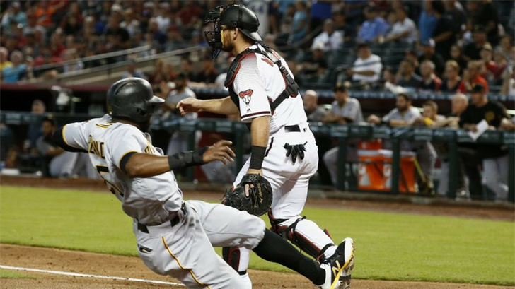 Pittsburgh Pirates' Gregory Polanco, left, scores a run as Arizona Diamondbacks catcher Jeff Mathis, right, waits for a late throw during the second inning of a baseball game Wednesday, June 13, 2018, in Phoenix. (Source: AP Photo/ROSS D. Franklin)